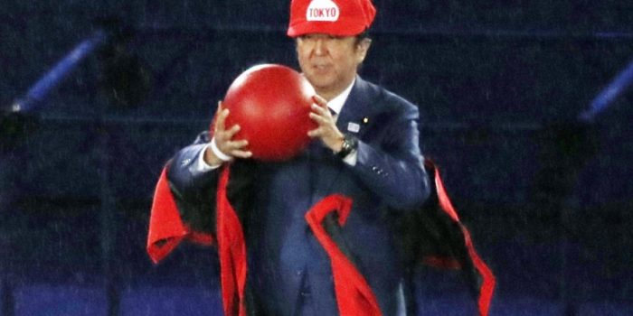 Japanese Prime Minister Shinzo Abe removes costume of the Nintendo game character Super Mario as he makes an appearance during the closing ceremony at the 2016 Summer Olympics in Rio de Janeiro, Brazil, Sunday, Aug. 21, 2016. Abe's brief but show-stopping appearance as Super Mario offered a tantalizing glimpse at Tokyo's plans for the 2020 games. (Yu Nakajima/Kyodo News via AP)